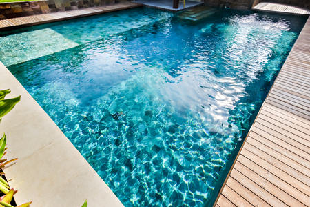 Light blue water swimming pool closeup in a luxury house giving deep look of the pool beside a wooden path