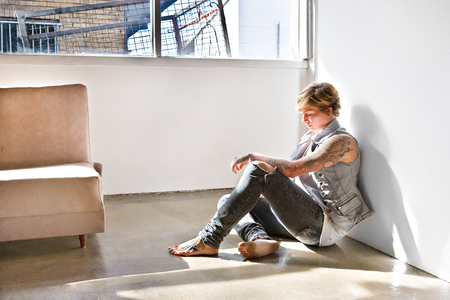 bend over: Young girl with a tattoo on her legs and arms sitting and bend over head down like thinking or showing sadness in a room with white walls and under the sunlight Stock Photo