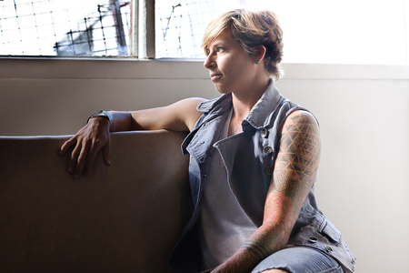 short haired: Short haired girl with tattoo on her hand, sitting on a chair and look away through the window showing the behavior of thinking about a problem