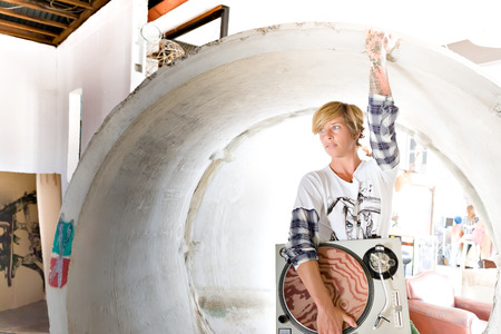 short haired: Short haired girl with a long sleeve t shirt holding a gramophone touching the drain with sunlight from the background Stock Photo