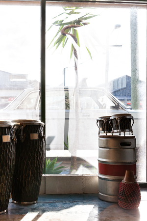 bongo: Musical instruments including bongo and drums in a room beside a glass window  which can bee seen the outside