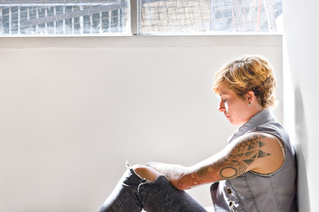 shorter: Cute girls with tattoos and a gold color shorter hair try to focus on a problem leans on the wall and sitting on the floor in a room beside a window Stock Photo