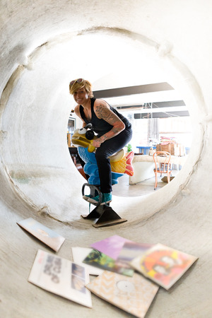 woman hanging toy: Lady with short hair having fun with toy horse in a concrete drain pipe with vinyl disks around