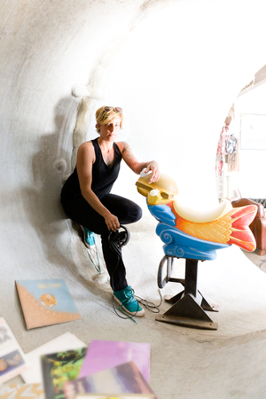woman hanging toy: Tattoo girl leans to a concrete pipe and holding a plastic toy like a riding fish in concrete pipe beside music albums Stock Photo