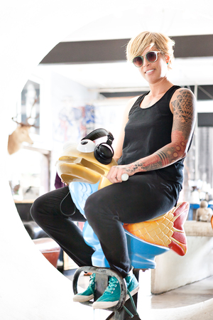 woman hanging toy: Young tattoo girl with a black dress and sunglasses rides a plastic toy fish and smile