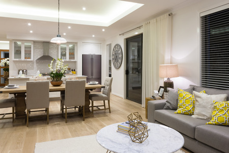Luxury living room beside a dining room attached to  the kitchen included pillows on sofas next chairs and table setup