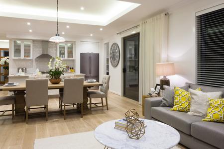 Luxe salon à côté d'une salle à manger attaché à la cuisine inclus oreillers sur les canapés et chaises à côté configuration de table Banque d'images - 59746518