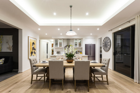 Modern dining room with hanging lamps on, there are chairs and table setup with fancy items on the wooden floor Banco de Imagens