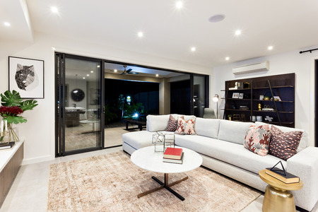 Modern living area with sofas and pillows attached to outside patio view at night