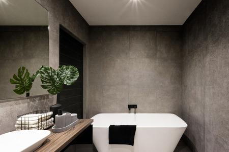 Cuarto de baño moderno de la pared hecha de azulejos de colores oscuros que cubrían la bañera y toallas cerca de la planta de lujo Foto de archivo