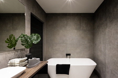 Moderna muro del bagno fatto in piastrelle di colore scuro che coprivano la vasca da bagno e asciugamani vicino alla pianta di fantasia Archivio Fotografico
