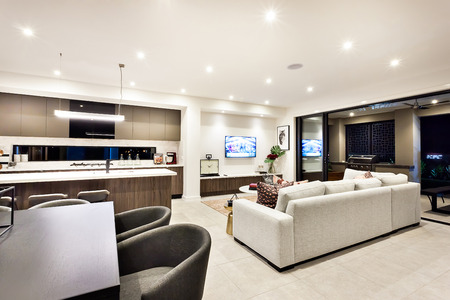 Modern living room with a television and sofas and pillows beside a dining area and kitchen, there is an entrance to an outside patio area Stock Photo