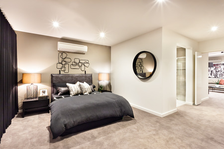 kingsize: Modern bedroom with a round mirror and hallway through the luxury house Stock Photo