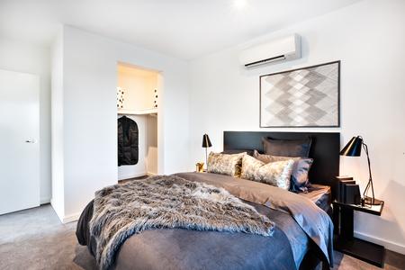 家や毛皮の毛布およびドレッシング ルームの隣に光沢のある枕を含むホテルのモダンなベッドの暗く、光沢のある装飾