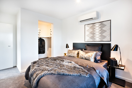 Dark and shiny decoration for a modern bed of a house or hotel, including a fur blanket and glossy pillows next to the dressing room