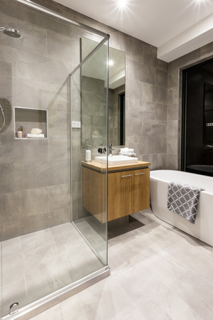 Modern bathroom with a shower area covered with glass  next to a wooden cupboard and tap beside a white bathtub