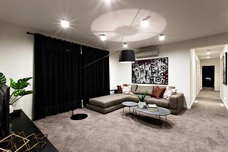 Moderne woonkamer met ruimte en hal met een zwart gordijn en hangende lichten naast banken met kussens, de tafel inclusief fancy plant en boeken Stockfoto