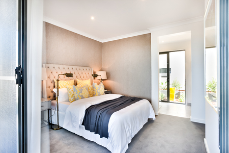 kingsize: Modern bedroom entrance and exit for an outside, the bedroom included yellow pillows and king-size bed with blankets with duvets beside lamps. The outside area illuminated with sunlight Stock Photo