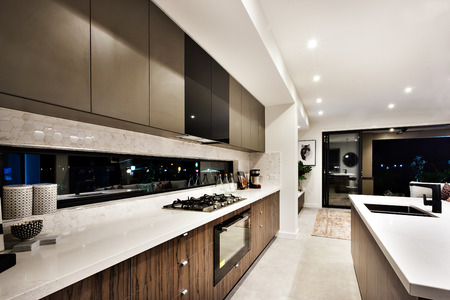 Modern cooking area, including a stove beside oven and countertop near pantry cupboards among the dark windows