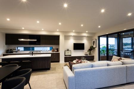 #59745697   Modernes Wohnzimmer Mit Stühlen Und Sofas Neben Den Tischen  Neben Einer Küche Mit Fenstern, Die Draußen Zeigen