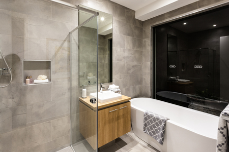washstand: Modern bathroom with a shower and bathtub next to a mirror and tap with washstand illuminated at night