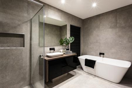 シャワー エリアとバスタブ付きのモダンなバスルーム蛇口近く派手な工場の横にある壁のミラーを含むと木製のカウンターとの暗い戸棚シンク 写真素材 - 59745664