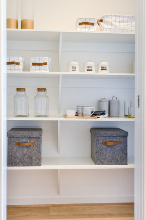 White wooden shelf included metal boxes and mugs with glass bottles next to leather bags in a modern house or market place Stock Photo