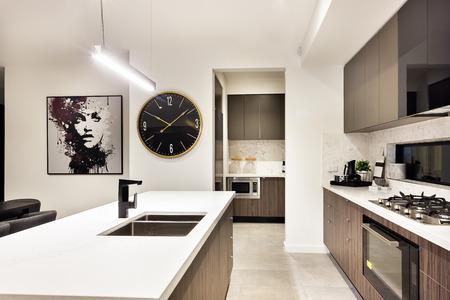 モダンなキッチン コンロ、オーブン、パントリーの棚の横に時計カウンターのクローズ アップ、タップとぶら下げチューブ ライトの下のシンク、