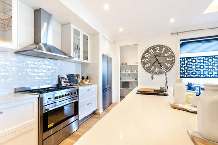 高級キッチン カウンター、ウィンドウの横にある大きな木製の時計の横にあるキャビネットの引き出しの横にあるオーブンの下コンロ クローズ ア 写真素材