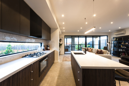 Modern kitchen illuminated with ceiling lights at day time, there is a white countertop in front of the windows that showed outside Banco de Imagens