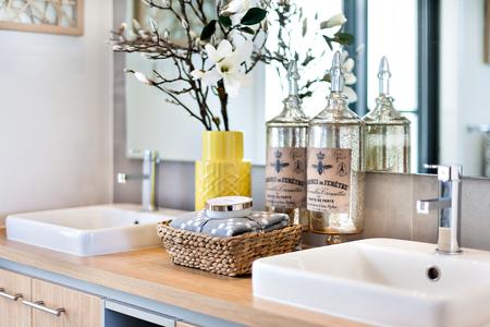 銀蛇口と花瓶の背後にあるミラーの横に木製のカウンターの上に白いシンクの横にタオルで石鹸、香水のボトルなどを含むモダンなバスルームのク 写真素材