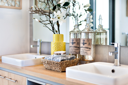 Modern bathroom closeup including soap and perfume bottles with towels next to silver faucet and white sink on the wooden counter top beside a mirror behind the flower vase