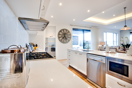 Luxury kitchen with modern items illuminated with sunlight included silverware next to the stove beside ovens under the countertop