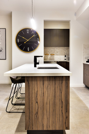 wall watch: Modern kitchen countertop made in wood with a wall watch and chairs of a luxury house