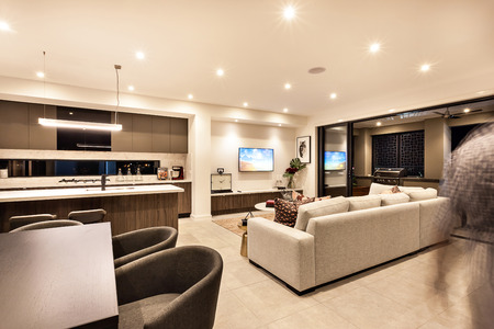 Luxury house interior with living room and the kitchen with tables, chairs, sofas with the flashing lights at night