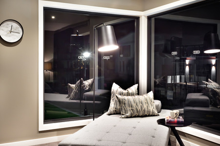 glass bed: Small bed and pillows beside a dark color glass window near a table Stock Photo