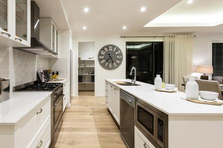 高級キッチン ストーブ、オーブン、カウンター、大きな木製の時計の横にある食器棚の間の別の部屋に廊下を