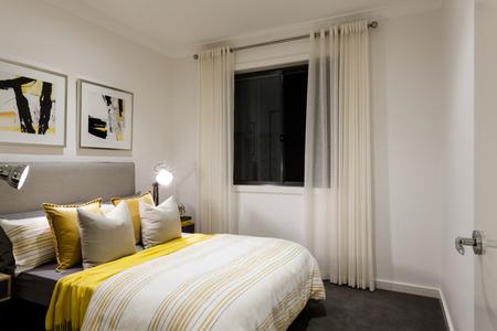 chambre classique d'une maison moderne avec des lampes de table sur à côté d'oreillers et un lit avec des couettes, il y a une fenêtre en verre noir recouvert d'un rideau