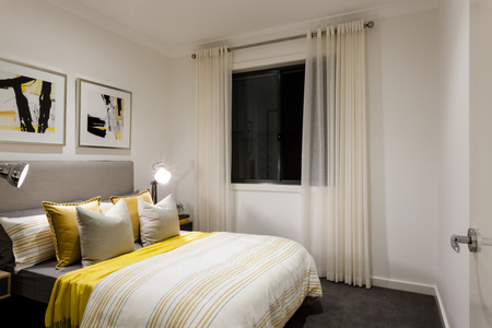 Classic bedroom of a modern house with table lamps on next to pillows and bed with duvets, there is a black glass window covered with a curtain