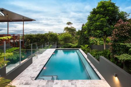 Modernes Hotel mit einem Pool unter dem hellen blauen Himmel mit den weißen Wolken, die schön verbreitet werden. Es gibt viele Bäume mit bunten Blättern wie im Wald. Der Zaun ist in Glas am Pool gemacht Standard-Bild