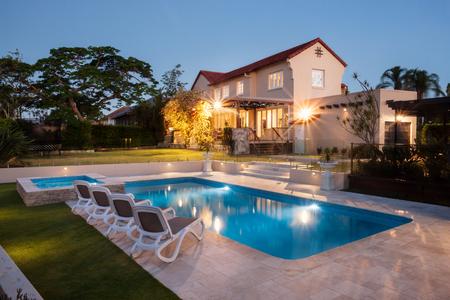 モダンなプールなど水辺の椅子、ライトで照らされた大きな家で