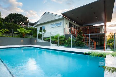 雲と青空の下では緑の木々 とモダンな家と豪華なプールサイドが塞がる、木製の階段と二階にフェンスがあります。