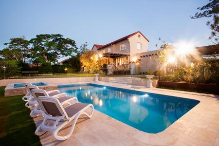 나무와 정원 주위에 번쩍이는 불빛과 함께 저녁에 호화로운 집과 수영장 장식, 의자가있는 물가에 녹색 잔디가 있습니다.