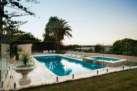 水辺の周りのガラス壁の横にある庭園、開花鍋でモダンなスイミング プールは素敵な内装