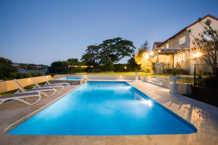 Luxury swimming pool with blue water at night with flashing lights from the large house garden