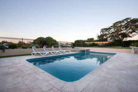 blue water pool of a modern house or hotel with a garden with trees and fence around, the floor is made gray color tiles.