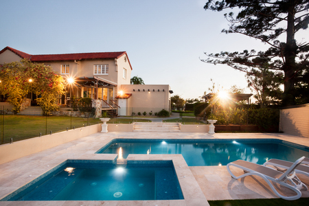 Modern swimming pool area with lights from a garden of a mansion, the waterside is divided to two parts and there is a chair to relax, a tall tree can be seen from the right