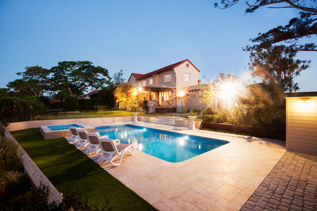 Modern house and a garden with a swimming pool illuminate with lights in a dark environment like evening, there is a green lawn and chairs around the poolside