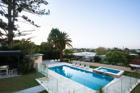 Modern swimming pool area view from a high angle shot which covered with glass panels and tress around, the area is filled with trees and house and it can be seen very beautifully with city view over the forest from the distance Stock Photo