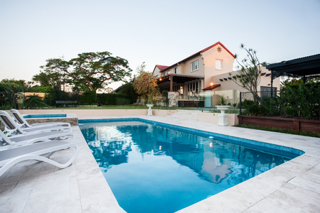 Swimming pool closeup next to chairs, modern house garden, the house or hotel is very big